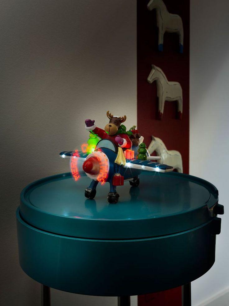 Underholdende og stemningsskapende fiberoptisk juledekorasjon med LED, sensor og timer fra Konstsmide. Figuren forestiller et reinsdyr i nissedrakt i et fly fyllt med gaver og teksten Merry Christmas på propellen.