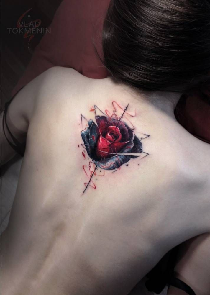 Graphic style red rose tattoo on the upper back.