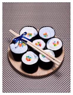 Sushi de bebé: compuesto por 2 bodis, 3 pañales y 2 baberos. Presentado en una bandeja de madera.
