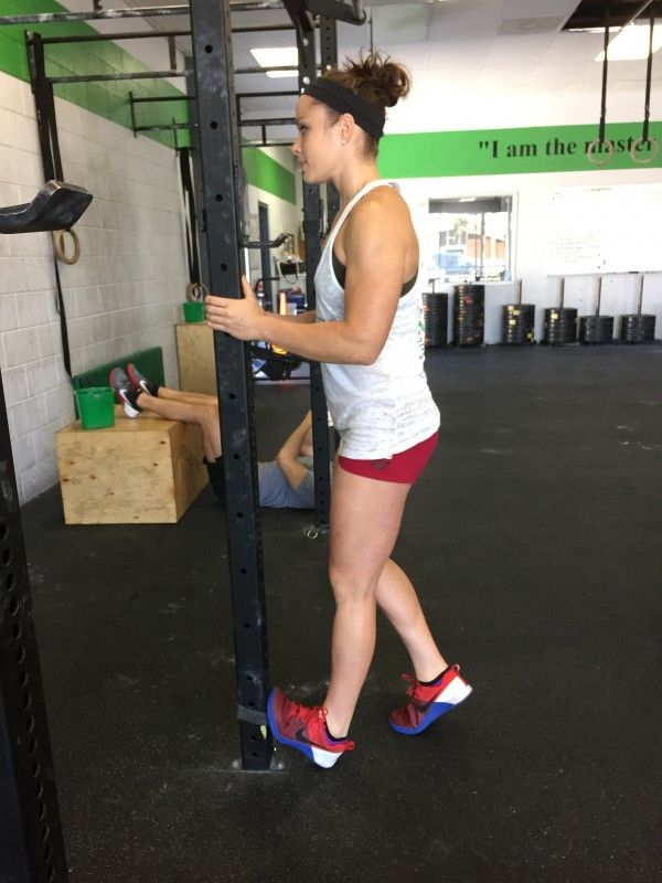 Coach Cat demonstrating ankle mobility at CrossFit Invictus in San Diego