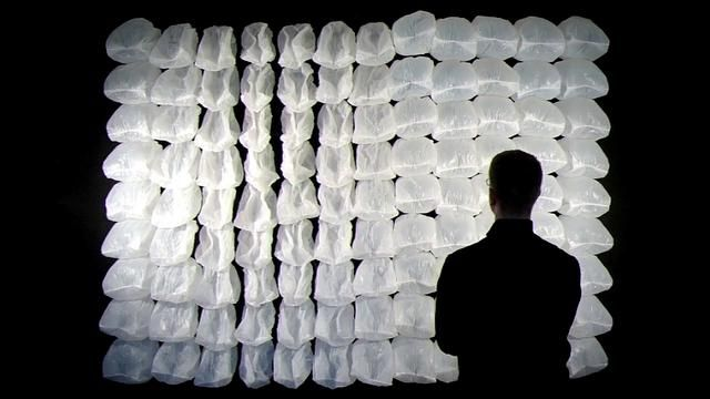 One Hundred and Eight – Interactive Installation by Nils Völker. One Hundred and Eight is an interactive wall-mounted Installation mainly made out of ordinary garbage bags. Controlled by a microcontroller each of them is selectively inflated and deflated in turn by two cooling fans.