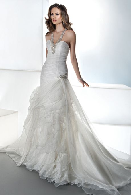 Demetrios - Illusions. Organza ruched fit and flare with jeweled halter neckline, and T-back. Skirt features side draping with beaded applique, layers of ruffled organza and attached train. Swarovski crystals and an attached train. Available in white and ivory.