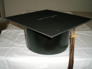 """Homemade Graduation Cap Centerpiece - all you need is a paper mache round hat box (approx. dimensions: 10"""" diameter, 6"""" tall),  black acrylic craft paint, a foam brush, black foam board, tassel, hot glue gun and sticks, craft knife, large black push pin or button. Easy to follow instructions at the blog (just click on the photo)."""