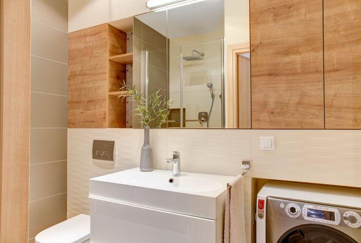 Drewniane elementy w aranżacji łazienki, w postaci obudowy szafek łazienkowych. Drewno w połączeniu z bielą płytek to klasyczne połączenie, które zawsze prezentuje się doskonale.