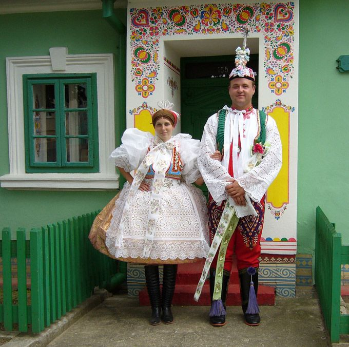 Couple in traditinal 'kroje' and a traditionally painted home, Moravia