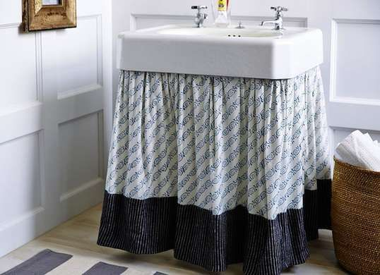 If you have a shelf beneath your pedestal sink, use a curtain to conceal the contents.