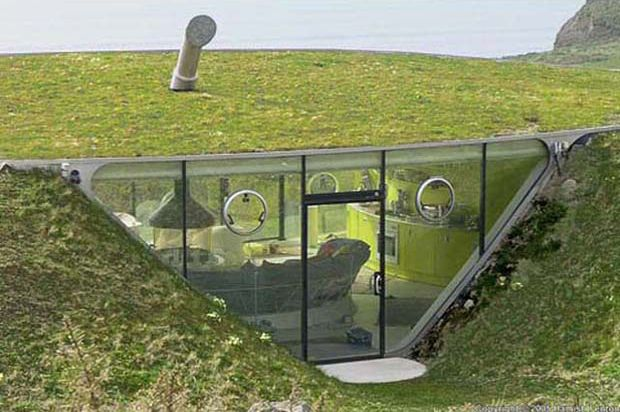 A glass house buried in the grass