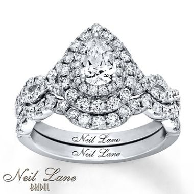 From Neil Lane Bridal®, this sensational bridal set for her brings red-carpet glamour to your wedding day. A pear-shaped diamond takes center stage, surrounded by two rows of dazzling round diamonds as part of the elegant engagement ring. Ribbons of round diamonds weave together along the band of the engagement ring with additional round diamonds flowing along the m