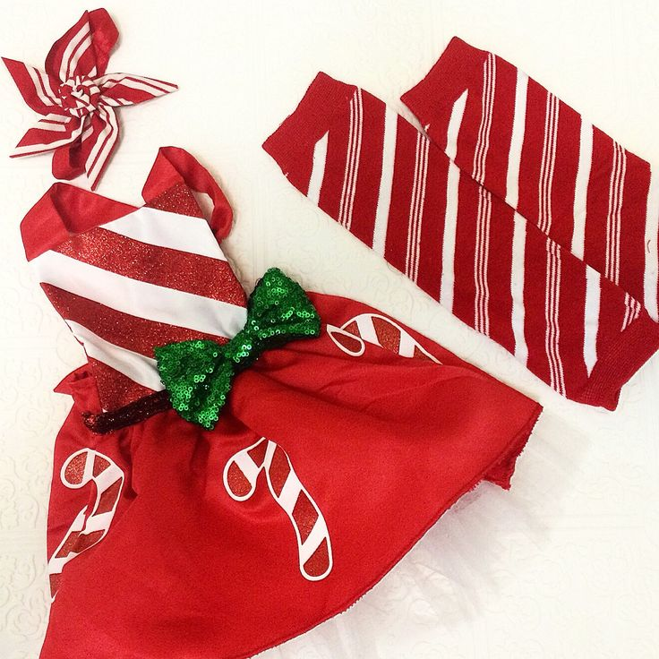 A babies first Christmas apron outfit set:  A cotton and polyester apron with a sparkling green bow.  The skirt has white tulle underneath.   There are 2 outfit sets available:  Option 1. Candy cane apron dress   headband   leg warmers  Option 2. Candy cane apron dress   headband   shoes  The leg w