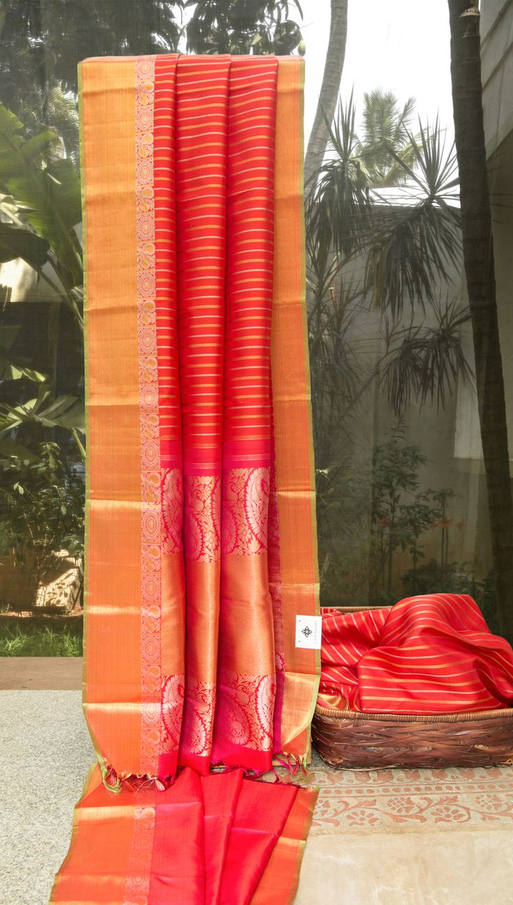 This apple red colored kanchivaram silk is exclusively designed by Lakshmi and has textured stripes on the body in gold zari and silver zari. The border is in apple red and has defined texturing a…