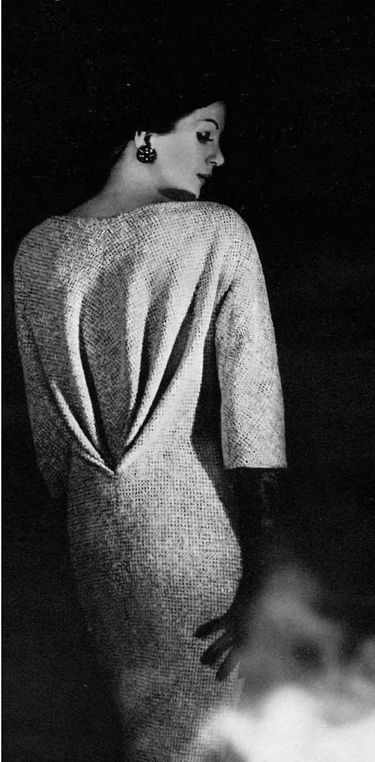 1960 Model in bias cut dress of grey and natural tweed, front is fully buttoned, back is draped into deep v, by Jean Dessès,