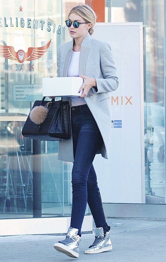 Gigi Hadid steps out in a white tee tucked into blue jeans, high top tennis shoes, a black structured bag, sunglasses and a grey coat.