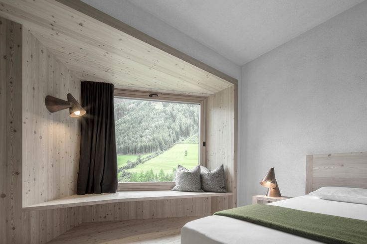 Italian studio Pedevilla Architects has completed an extension to a traditional Alpine hotel, comprising a monolithic blackened-timber volume with windows that jut from the walls and roof to optimise mountain views.