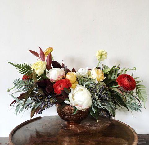 Potencia la decoración en invierno combinando los rojos y verdes tradicionales con amarillos y naranjas. Este ramo brillante trae a la mente paseos en trineo el día de Navidad y chocolate caliente. Vía Pollen