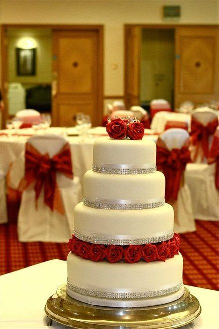 RED ROSES WEDDING CAKE RED SASHES ON CHAIRS N SUM BLACK TOO  (replace red with plum flowers) i like the rhinestone thingees