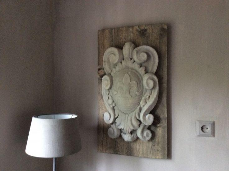 Prachtig ornament op houten paneel. Het ornament is van beton. Staat prachtig in sobere en landelijke inrichting.  Hoog: 72 cm. Breed: 39 cm.