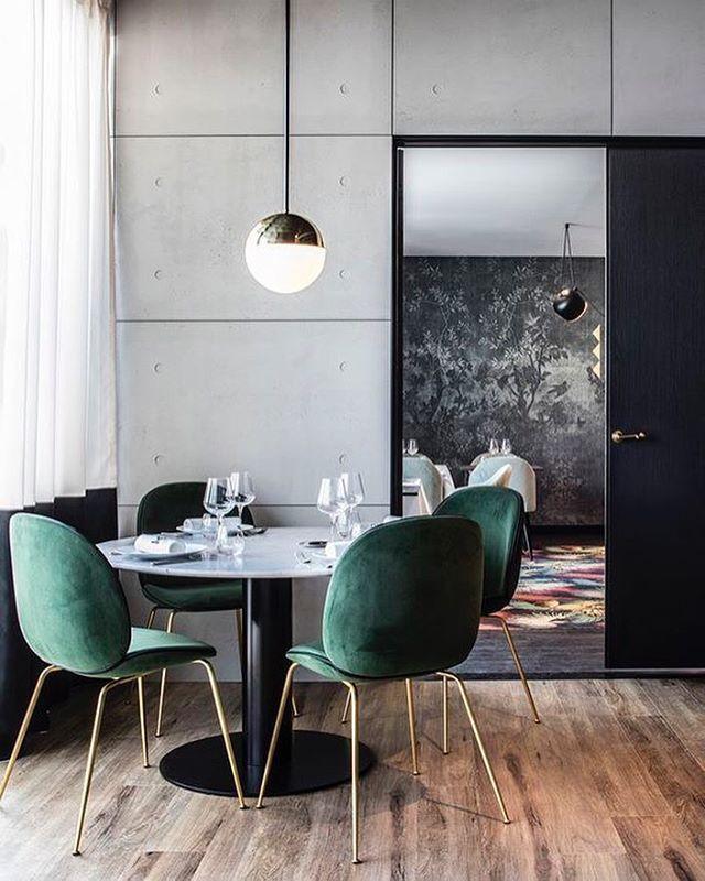 Runt bord o gröna stolar i köket