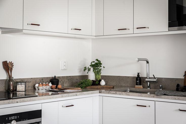 I det smakfulla köket finns allt man kan önska sig och lite till. Framför allt finns här rejält med utrymme och förvaring. Stilsäkra släta luckor i grått med läderlindade handtag, vacker kalkstensbänk med underlimmad ho och designblandare.