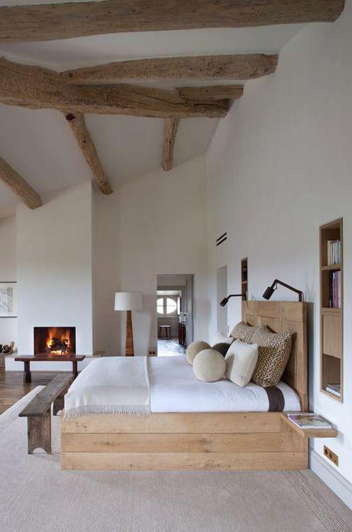 Slaapkamer met houten balken aan het plafond en een haardvuur voor een warm effect #woonstijl #landelijk