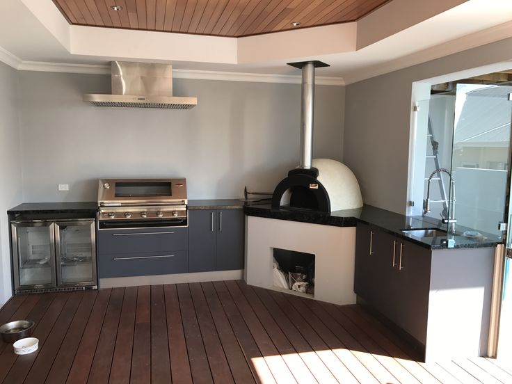 Alfresco kitchen with a wood fired pizza oven, Black Pearl granite and Eleganz perspex doors