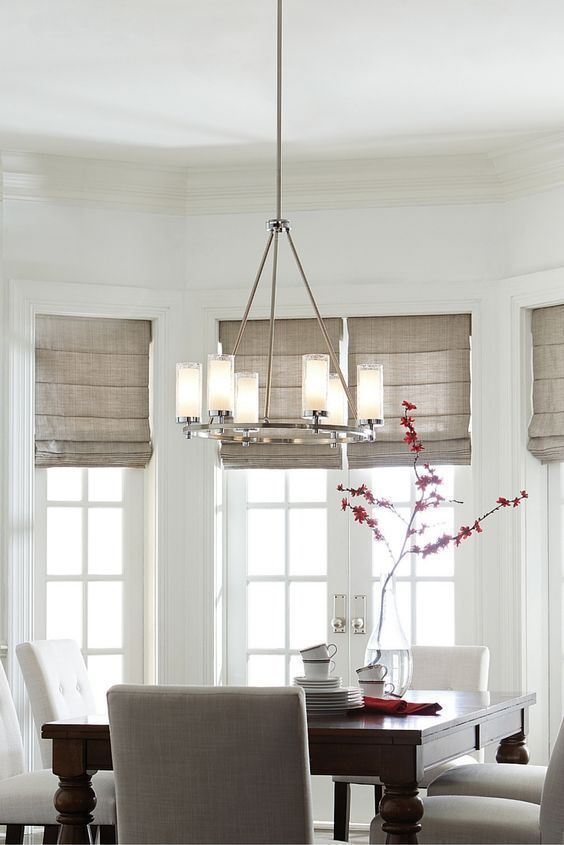 With a modernized wagon wheel silhouette, the Jonah lighting collection by Feiss has cylindrical, Crackled glass shades with White inner glass to create soft light as seen in this dining room. Further updating the period inspired aesthetic is the two-tone