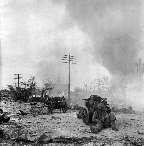 U.S. Marine resting behind cart on rubble-strewn street during battle to take Saipan from occupying Japanese forces.  What One Photographer Saw at the Battle of Saipan | TIME