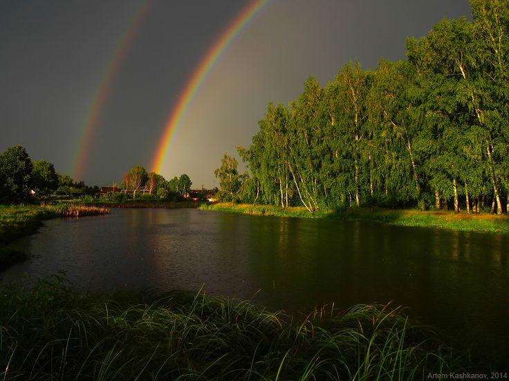 Фотография яркой двойной радуги. Красивый деревенский пейзаж с двойной радугой.