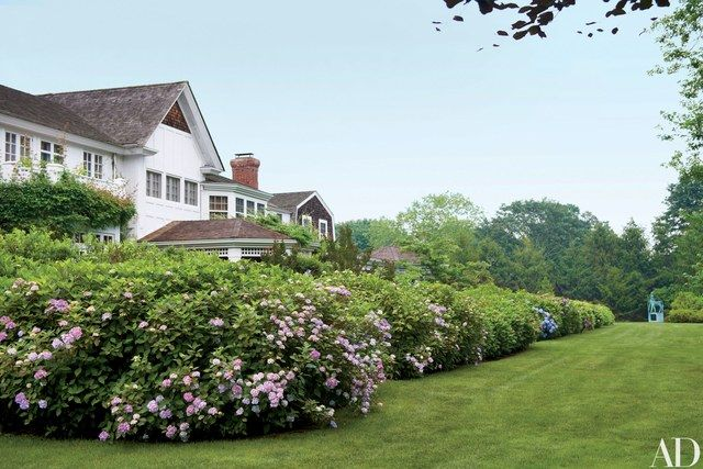 'Pink Beauty' hydrangeas engulf the rear of the 1990s dwelling, which looks as if it had been built in stages over centuries—a shingled Dutch Colonial section at right, a central block recalling the late-19th-century country houses of McKim, Mead & White, and an Arts and Crafts wing that could have been added around 1905.