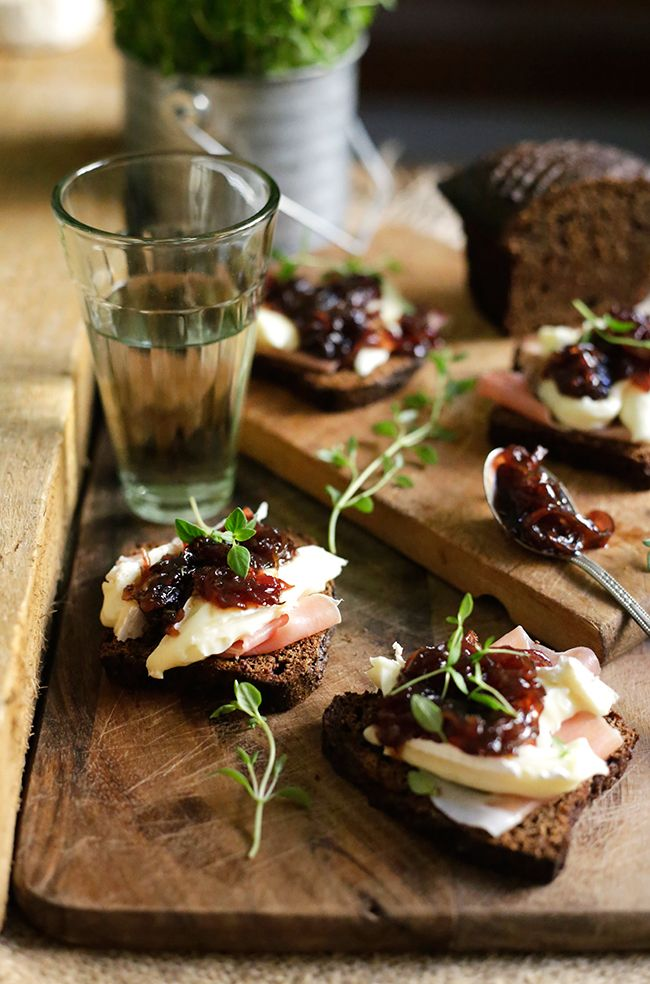 Sweet red onion jam on pieces of rye bread, with jamon serrano and brie cheese.