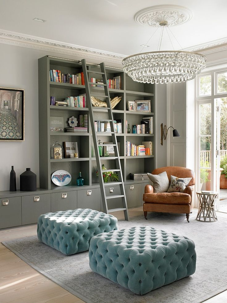 London home: Contemporary, minimalist greenish-gray built-in shelves and storage cabinets; carmel leather club chair; powder blue tufted ottoman benches; tall & ornate crown moulding; gorgeous contemporary chandelier