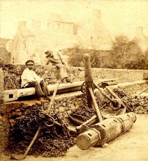 Deux enfants jouent sur le mur, le guindeau en bois cerclé de fer,  une vieille ancres à jas de bois aux extrémités de section ronde et des ancres à jas démontable en fer