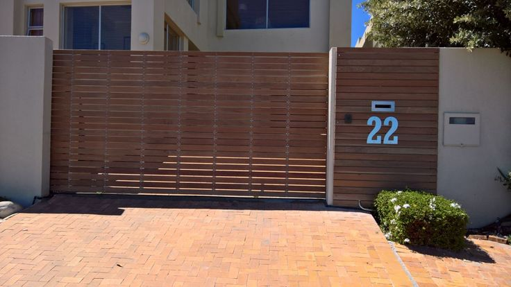 Galvanized Mild Steel Gate Cladded in Balau Wood, Manfuactured and Installed by Sterianos Engineering cc. Sterianos Engineering also manufactured and installed the stainless steel letter box cover and house number.