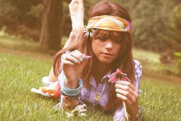 Девушка хиппи лежит на траве, в руке держит цветок