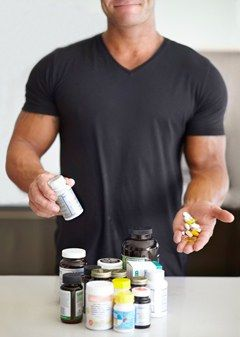 Fit Man Displaying Different Types of Supplements
