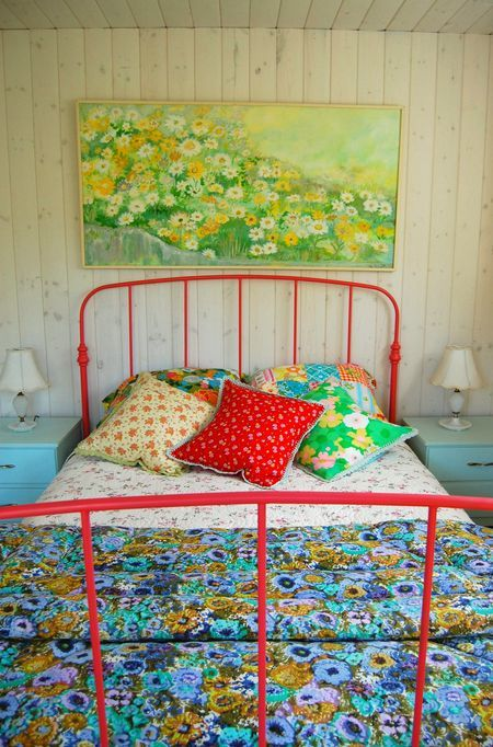 Red Metal Bed. Sunny Floral Painting. Pretty Floral Quilt in Hues of Blue.