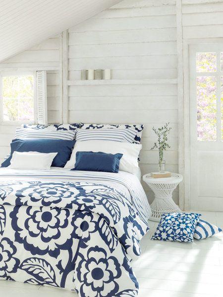 Dormitorio con colcha azul y blanca