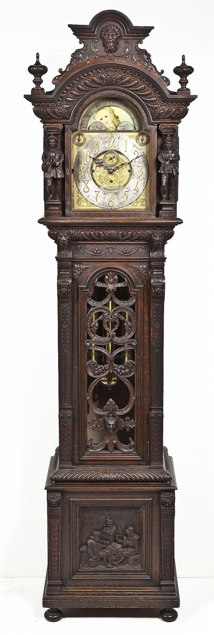 """Sold: $17,000 - Tiffany & Co. Tall Case Clock. Nine tube tall case clock. Dial signed Tiffany & Co. Oak case profusely carved with full figure musicians on hood and tavern scene on base. Side columns with lions' heads and putti. Door with scrollwork, fruit and satyr head. Silvered chapter ring over ornate face. Moon phase. Subsidiary seconds. Westminster eight bell chime. Nine tube. Tubes marked """"Walter Durfee"""". Late 19th century."""