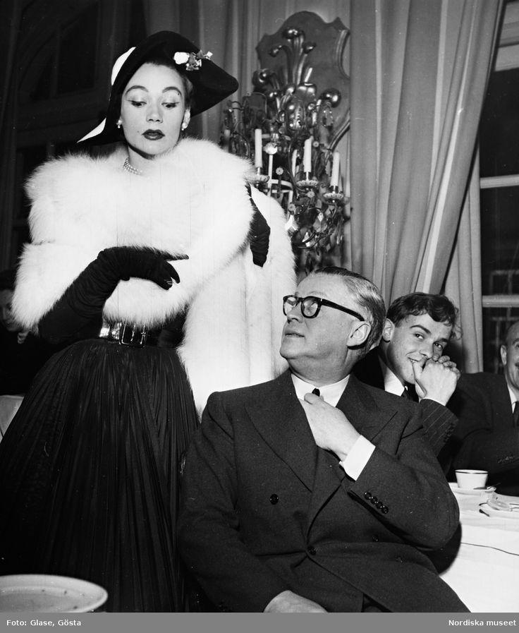 Kvinna i vit pälsboa, svarta aftonhandskar, hatt med garnityr och svart kjol, bredvid man i kostym på restaurang. Fotograf: Gösta Glase, ca 1950-1959