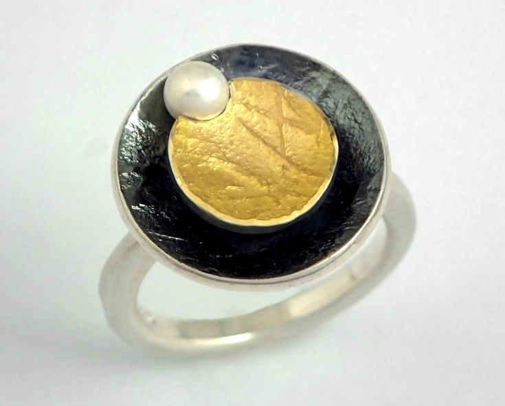 Modern circular gold and oxidized silver ring decorated with a pearl and rough golden surface by TomisCraft on Etsy