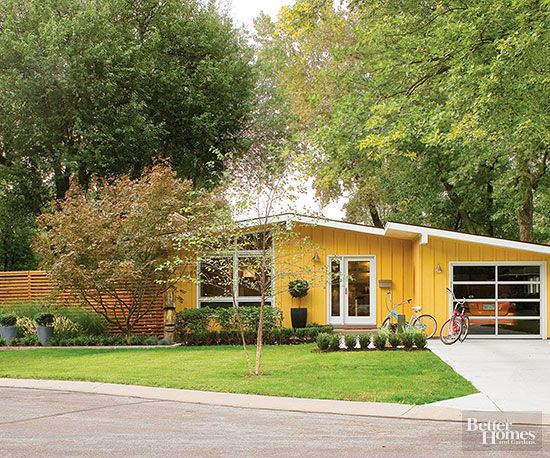 Bright, cheery, and just plain fun, the facade of this ranch-style home offers lots of inspiration. For starters, the pretty collection of plants, including low-growing shrubs, are a minimalist, elegant complement to the bright yellow color. They also serve to accent the Asian-inspired fence, a low-slung facade that plays up the landscape without completely blocking the view./