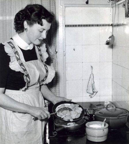 Onbekend | Huisvrouw met schort voor aan het aardappelen bakken in de keuken. De zoutpot staat naast de pannen. Plaats onbekend,1958.
