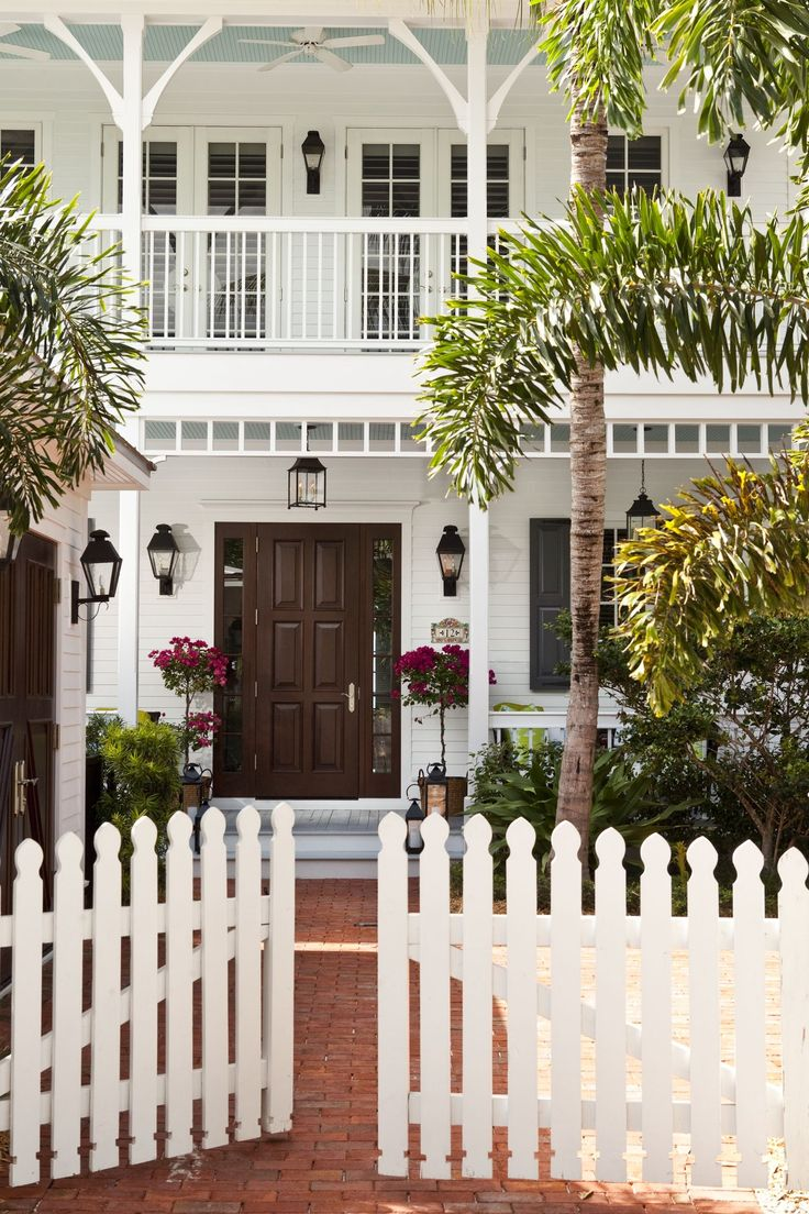 A picket fence marks the entrance to this white Clapboard Key West Beach house, which was renovated with an eye to making it brighter and slightly more formal  Architectural Details  Cottage  Entryway by Taylor & Taylor