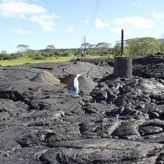 About 20 journalists trudged across the cracked, black lava at the town of Pahoa's waste transfer station, where the flow came within feet of burning structures before losing momentum and stalling.The lava's surface there had cooled and hardened but was still releasing small, warm columns of air, the Hawaii Tribune-Herald reported.