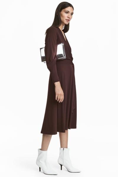 Robe de longueur genou en jersey crêpé. Modèle croisé et drapé en haut. Découpe à la taille soulignée par ceinture à nouer amovible. Manches longues.