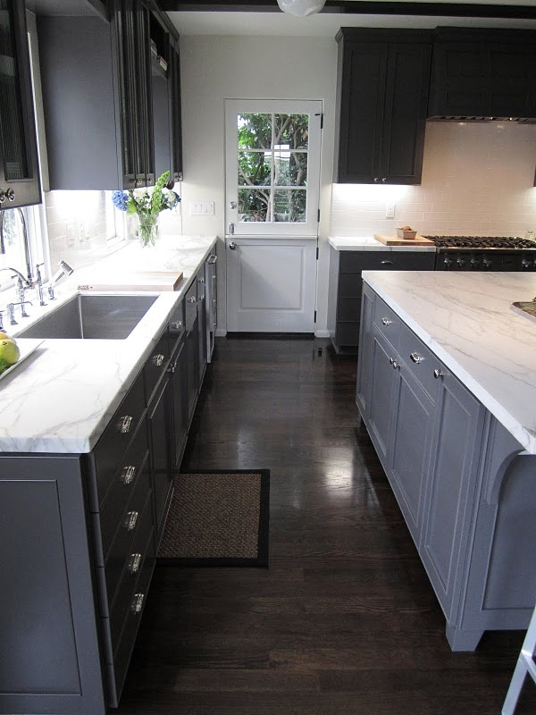 Talk about making the most of a small space! Galley kitchen with Dutch door, grey cabinets, and carrera marble counters.
