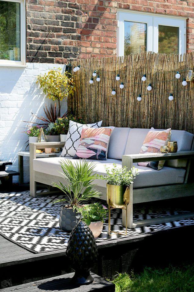 Swoonworthy Boho Garden Makeover featuring reed screening, outdoor sofa and outdoor rug