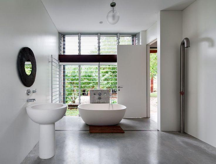 baño moderno, lavabo de pie y bañera exenta de diseño, zona de ducha abierta, suelo microcemento