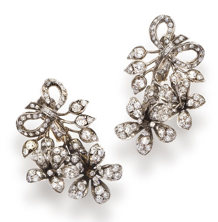 A pair of diamond earclips  each designed as a floral spray of old European and single-cut diamonds; estimated total diamond weight: 7.00 carats; mounted in silver; length: 1 3/4in.