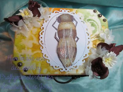 For this weeks challenge I have decorated another wooden box, I used my Bee digi from LEJ DesignsI have used the same technique as last time on the colouring, I coloured the image with Graph'it Markersand then used the blender pen to remove colour where the wings where then highlighted with a white gel pen, added clear glitter with a quickie glue pen and then added 3d glaze on top then layered it on to a Spellbinders die cut frame. the background on the box was made usingPanPastelsand…