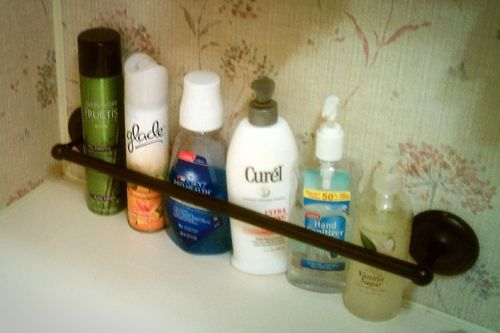 Instead of a towel rack...use elastic band with hooks. Its out of the way until you are ready to travel, pull it around bottles when its time to move!
